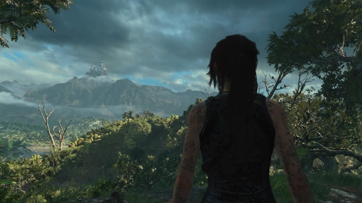 Lara looks out across a valley, there is a mountain in the distance
